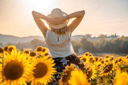 Ragazza felice con cappello di paglia guarda il tramonto in un campo di girasole Fototapeta