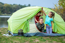 Three Children Looking Out Tent And Smiling In Camping Site Close To River