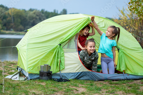 Three children looking out tent and smiling in camping site close to river Fotobehang