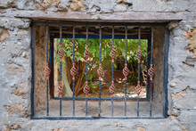 Antique Uneven Beige Stone Wall. It Has A Rectangular Recess, Which Is Closed By A Forged Black Lattice With Decorative Copper Elements.