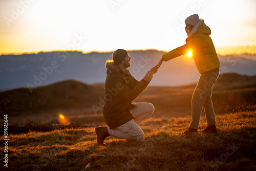 Fototapeta Silhouettes of a man making a marriage proposal to his girlfriend on the mountain peak at sunset