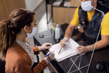 Female Customer With Protective Face Mask Signing Documents At Auto Repair Shop.