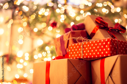 Christmas presents under the tree, full of bright lights of garland Fototapet