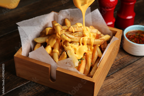 Fotografering Man pouring melted cheese sauce on French fries in a wooden box