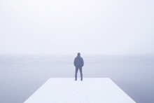 Young Adult Man Standing On Snow Covered Footbridge And Looking Far Away At Lake. Mist Over Frozen Water. Foggy Air. Winter Day. Empty Place For Text, Quote Or Sayings. Back View. Copy Space.