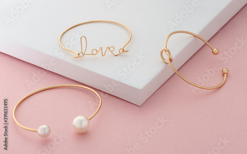 Fotografia love word and knot shape golden bracelets on white and pink colors background