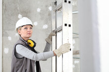 Woman Construction Worker Builder Portrait Wearing White Helmet And Hearing Protection Headphones, Holding A Ladder On Interior Site Building Background With Scaffolding