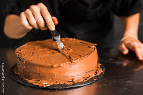 Men's hands decorating chocolate cream on cake by spatula Fotobehang
