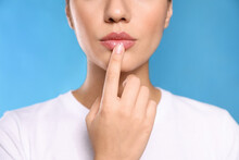 Woman With Herpes Touching Lips On Light Blue Background, Closeup