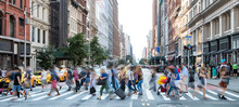 Busy Street Scene In New York City With Groups Of People Walking Across A Crowded Intersection On Fifth Avenue In Midtown Manhattan