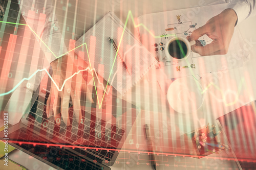 Multi exposure of man's hands typing over computer keyboard and forex graph hologram drawing. Top view. Financial markets concept.