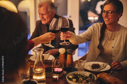 Obraz Family enjoying Christmas dinner at home - fototapety do salonu