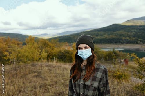 Obraz Woman tourism travel medical mask Autumn forest nature - fototapety do salonu
