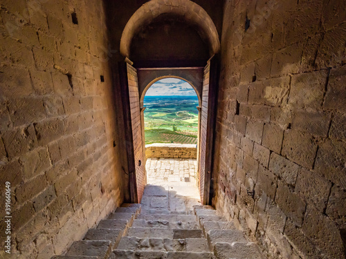 Amazing shot of a stone made historic building door opening with a picturesque landscape view