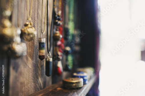 Closeup of crystal necklaces hanging on a wooden surface under the lights with a Fotobehang