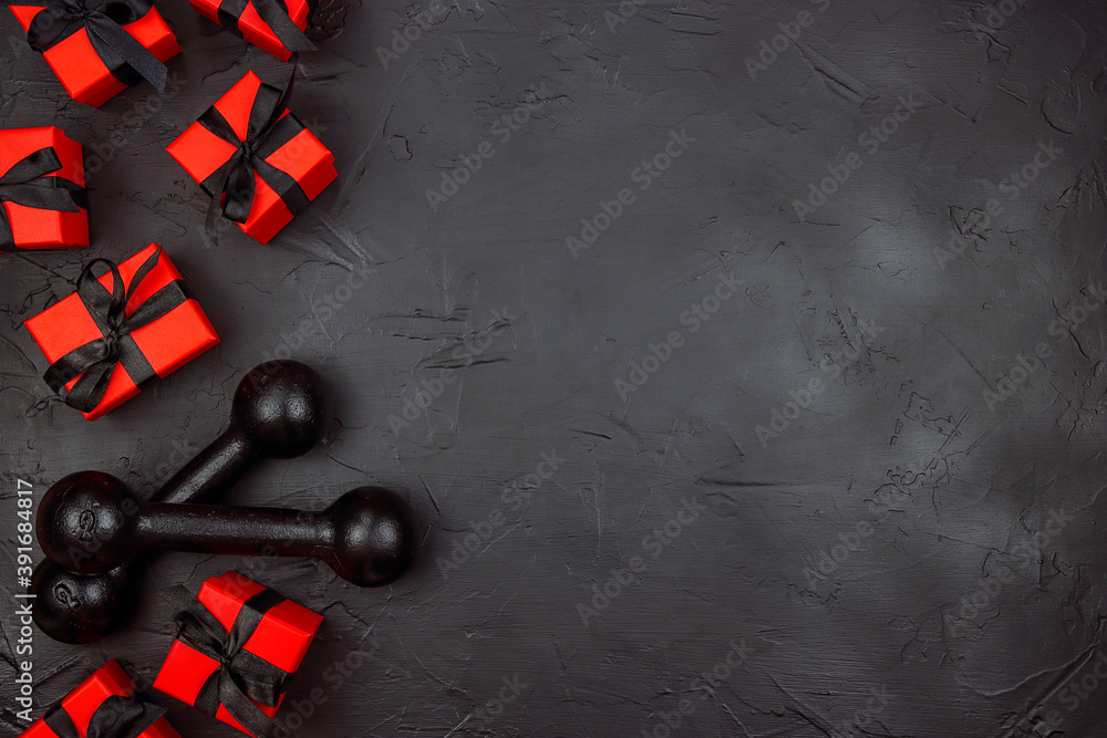 Fototapeta A pair of dumbbells and red gifts with black ribbons on a black background.  Holiday fitness sale or black friday concept.