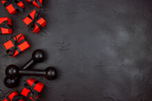 A Pair Of Dumbbells And Red Gifts With Black Ribbons On A Black Background.  Holiday Fitness Sale Or Black Friday Concept.