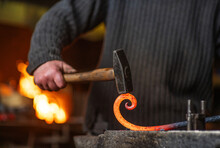 A Close-up Image Of A Blacksmith's Hands Forging A Spiral From A Red-hot Billet Against The Background Of A Forge. Handicraft Concept