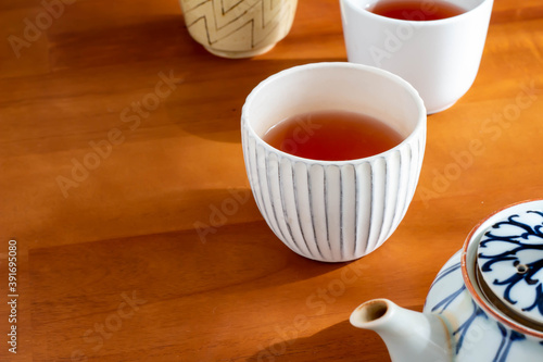 Tela 日の当たるテーブルに置かれた急須とほうじ茶の入った湯飲み