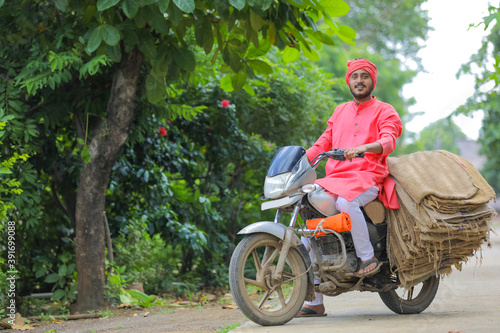 Photo Young indian farmer collect sackcloth bag on motor bike