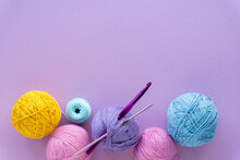 Colored Yarn Balls For Crocheting On A Lilac Background, Top View