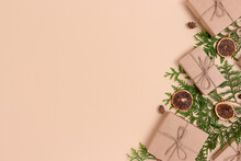 Wrapped Christmas Gifts And Coniferous Branches On A Beige Background. Zero Waste Holidays Concept With Place For Text.