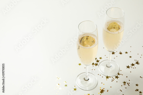 Vászonkép Champagne glasses and glitter on white background