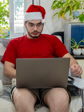 Young Man In A Red Shirt And Santa's Hat, Works On His Computer Sitting On A Sofa.