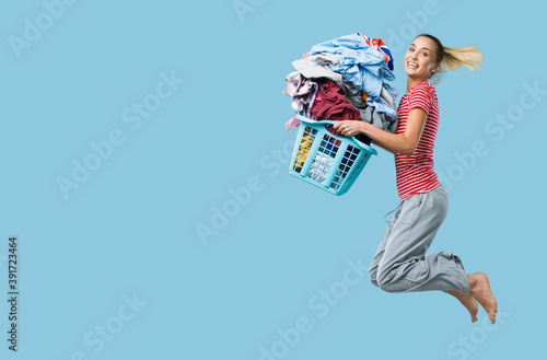 Fotografiet Happy woman doing laundry and jumping