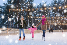 Christmas, Family And Leisure Concept - Happy Mother, Father And Daughter At Outdoor Skating Rink In Winter Over Snow