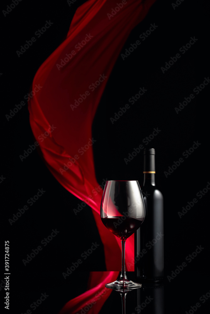 Fototapeta Вottle and glass of red wine on a black reflective background.