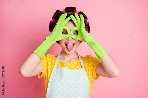 Playful girl make okay sign binoculars show tongue out wear green latex gloves isolated over pastel color background