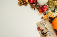 Autumn Flat Lay Composition With Copy Space On White Background. Pumpkins, Apples, Cones, Leaves, Acorns, Chestnuts, With Fork And Knife On A Jute Material For Thanksgiving Dinner.