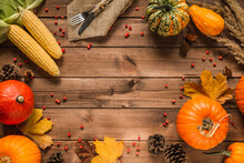 Autumn Flat Lay Composition Frame With Copy Space On Wooden Background. Pumpkins, Cones, Leaves, Corn On The Cob, With Fork And Knife On A Jute Material, For Thanksgiving Dinner.