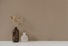 Retro Bottle With Dry Wheat / Rye Stalk Against Pastel Beige Background. Minimal Modern Interior Decoration Concept.