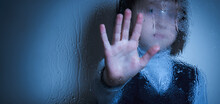 Protect Children And Young Underage People From Violence, Exploitation, Abuse, And Neglect Concept. Young Girl Showing Stop Gesture From Behind Wet Glass. Copy Space For Design Or Text.