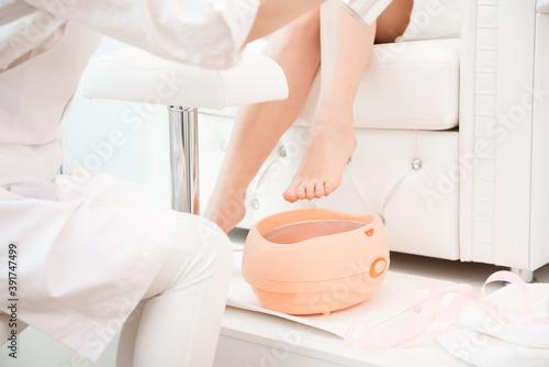 Fotografie, Obraz Wax bath for feet at beauty spa salon