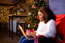 Afro Woman Shopping Online On Laptop In Cozy Christmas Interior.Preparing To Xmas, Bying On Winter Sales
