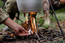 Hand Of Man Sets Fire Under Cooking Pot In Forest.