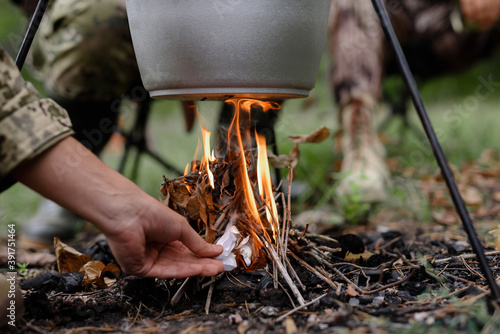 Hand of Man Sets Fire under Cooking Pot in Forest. Fotobehang
