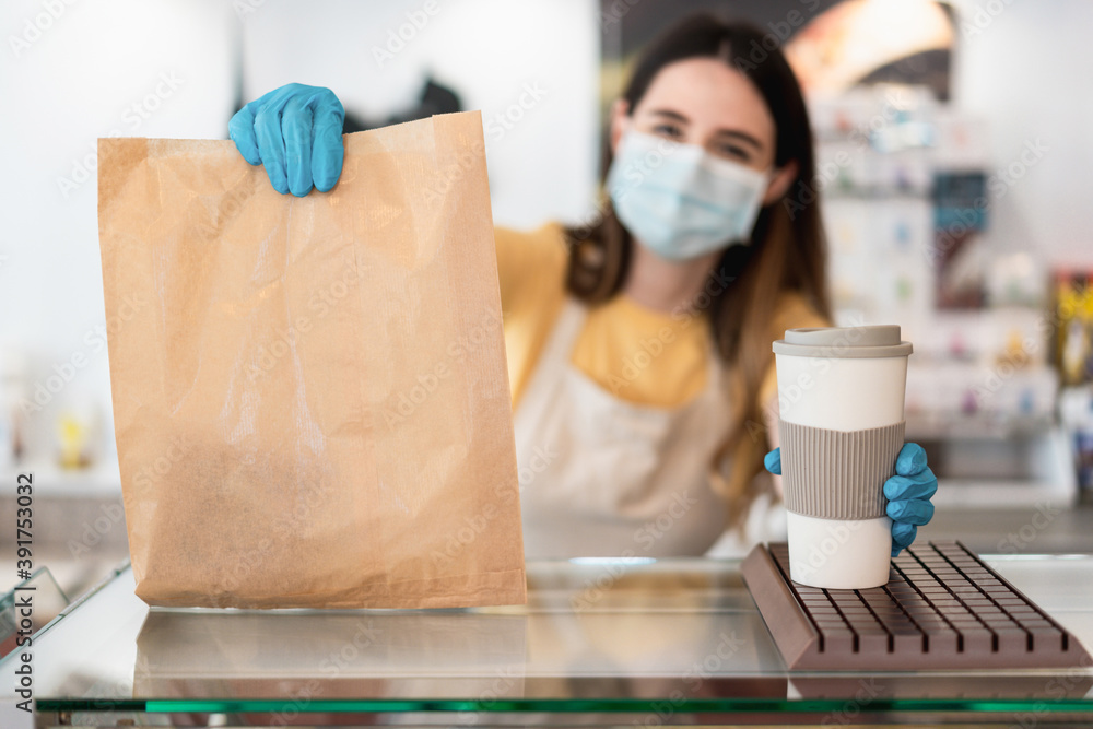 Fototapeta Young worker woman delivering takeaway food with face mask - Focus on coffee cup