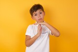 Cute Caucasian little boy standing against yellow background  feels tired and bored, making a timeout gesture, needs to stop because of work stress, time concept.