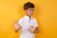 Afraid Cute Caucasian Little Boy Standing Against Yellow Background , Makes Terrified Expression And Stop Gesture With Both Hands Saying: Stay There. Panic Concept.