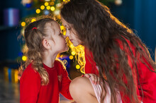Two Cute Girls Look At Each Other Lovingly Together In A Christmas Interior With A Christmas Tree. Christmas And New Year Concept
