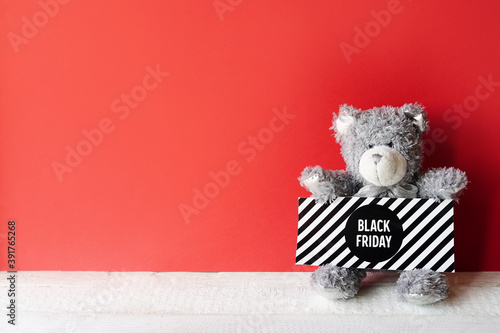 Fotografía gray teddy bear with sign black friday on red background, copy space