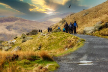 Group Of Hikers, Hiking On Snowdon Mountain, Dramatic And Mystic Weather With An Eagle Flying Over
