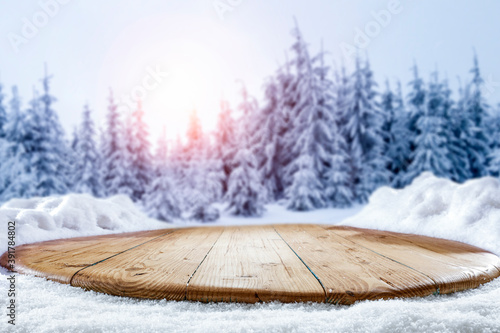 Snow on a wooden table surrounded by a beautiful winter setting sun with a landscape background