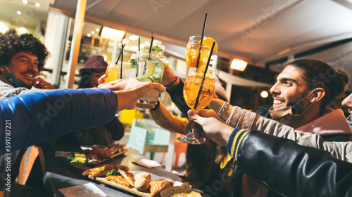 Fotografia Group of friends drinking at cocktail bar with open face masks - Happy young people having fun together toasting drinks at restaurant - New normal lifestyle concept