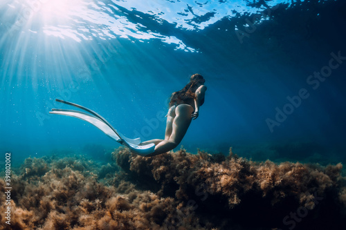 Freediver young woman with white fins glides undersea with sun rays Fototapet