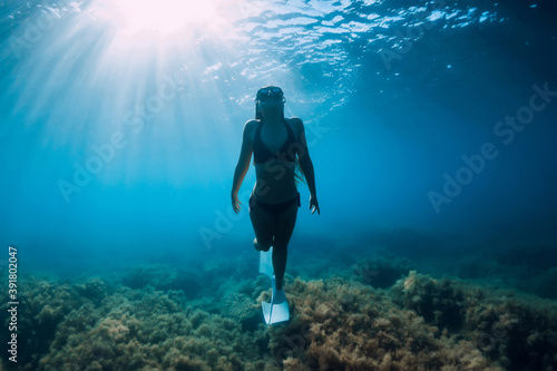 Canvastavla Freediver young woman with white fins glides undersea with sun rays